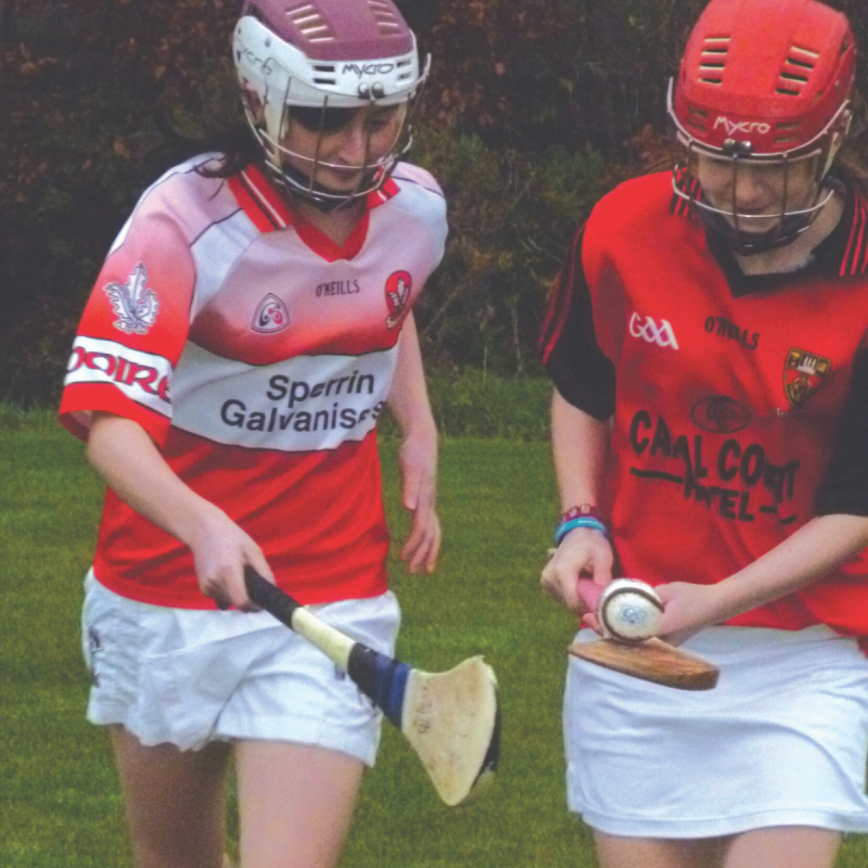 Two girls playing hurling with helmets