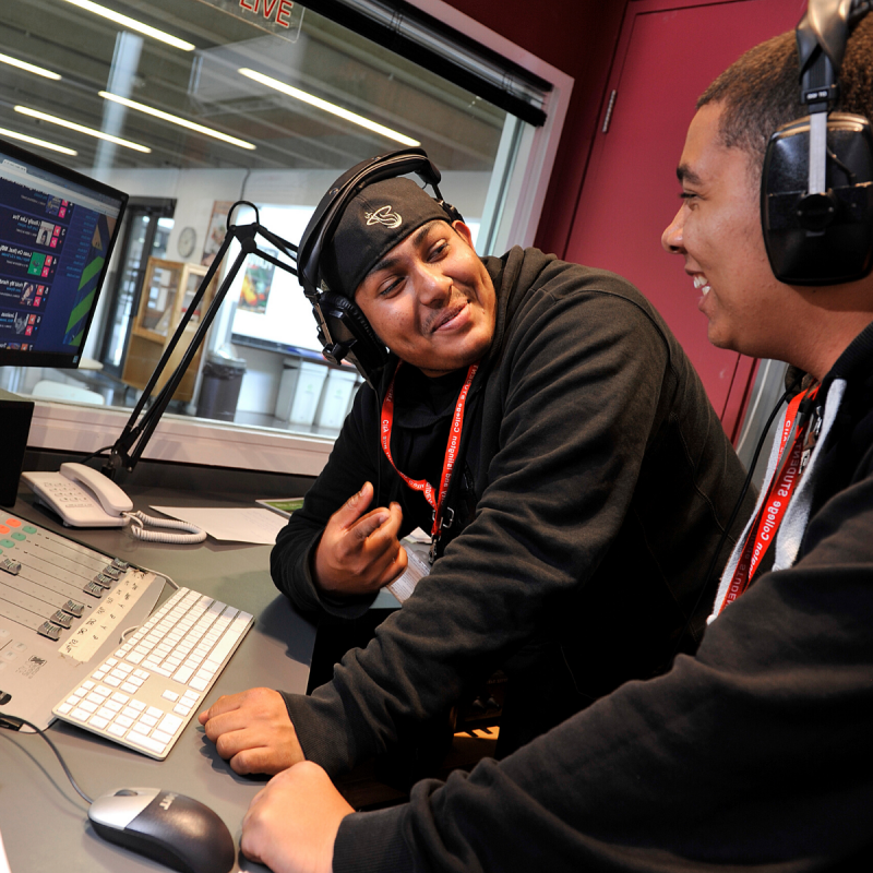 Two young men in a radio station booth