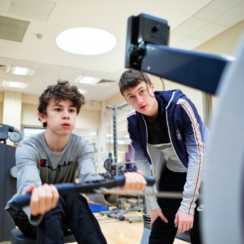 Two young men in gym in rowing machine