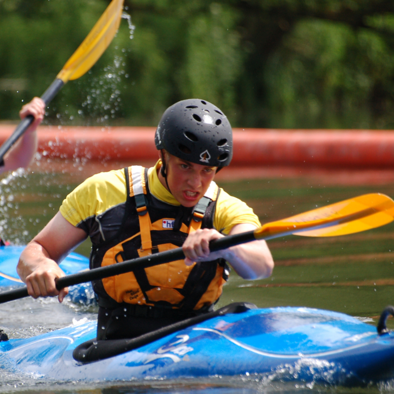 Young male participant kayaking on river